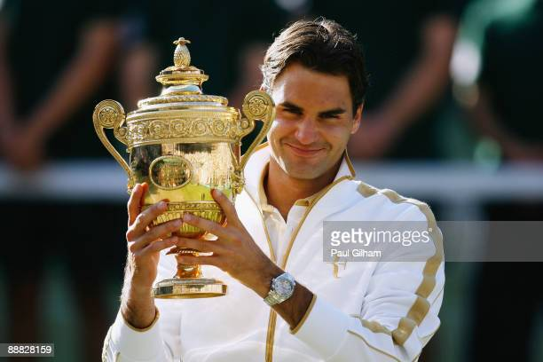 Roger Federer of Switzerland celebrates victory with the trophy after the men's singles final match against Andy Roddick of USA on Day Thirteen of...