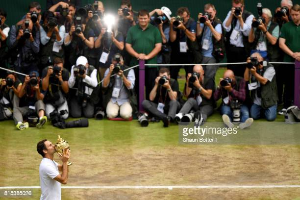 Roger Federer of Switzerland celebrates victory with the trophy as he poses for photographers after the Gentlemen's Singles final against Marin Cilic...