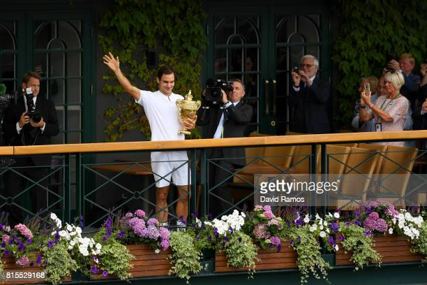 Roger Federer of Switzerland celebrates victory with the trophy on the balcony after the Gentlemen's Singles final against Marin Cilic of Croatia on...