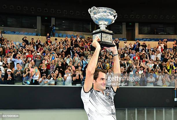 Roger Federer of Switzerland celebrates with fans in Margaret Court Arena as he holds the Norman Brookes Challenge Cup after winning the Men's Final...