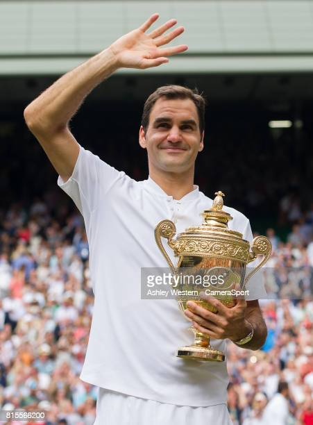 Roger Federer of Switzerland celebrates with the trophy after his defeat of Marin Cilic of Croatia in their Gentlemen's Singles Final at Wimbledon on...