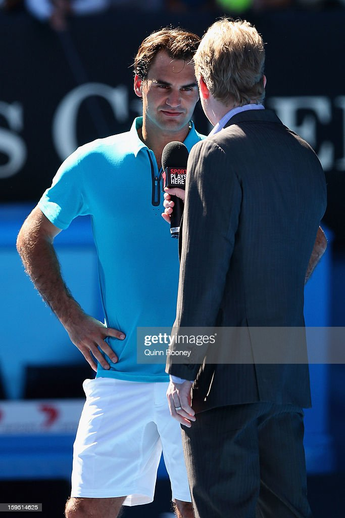 Roger Federer of Switzerland chats to Channel Seven commentator and former player Jim Courier after winning his first round match against Benoit Paire of France during day two of the 2013 Australian Open at Melbourne Park on January 15, 2013 in Melbourne, Australia.