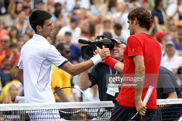 Roger Federer of Switzerland congratulates Novak Djokovic of Serbia after Djokovic won their match during Day Thirteen of the 2011 US Open at the...