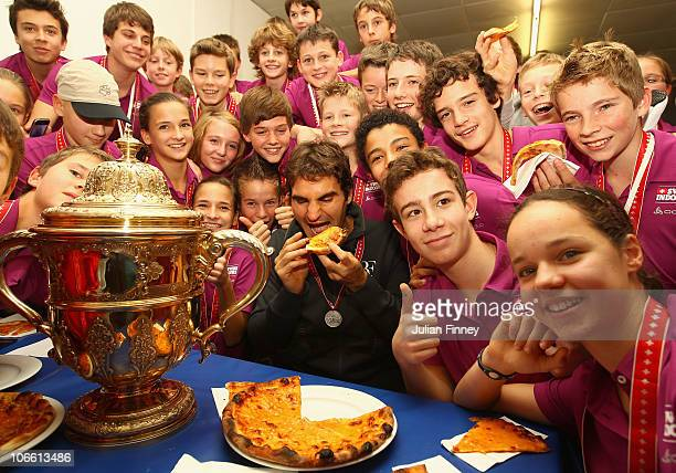 Roger Federer of Switzerland enjoys some pizza with the ball kids after defeating Novak Djokovic of Serbia in the final during Day Seven of the...