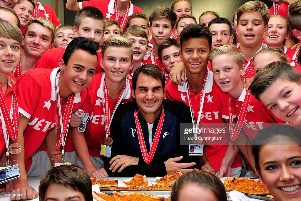 Roger Federer (C) of Switzerland hands out pizza as he celebrates with the ball boys winning the final match of the Swiss Indoors ATP 500 tennis tournament against Rafael Nadal of Spain at St Jakobshalle on November 1, 2015 in Basel, Switzerland