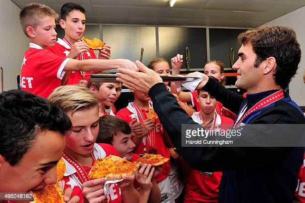 Roger Federer of Switzerland hands out pizza as he celebrates with the ball boys winning the final match of the Swiss Indoors ATP 500 tennis...