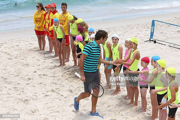 Roger Federer of Switzerland high fives junior surf lifesavers during a Hopman Cup preview at Cottesloe Beach on December 30 2016 in Perth Australia