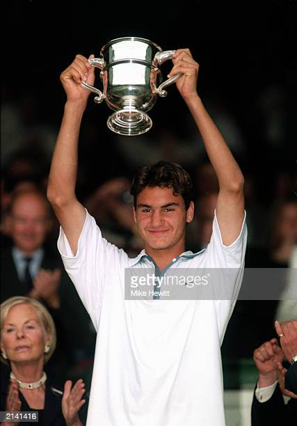 Roger Federer of Switzerland holds aloft the Boys Singles trophy after his win over Irakli Labadze of Georgia in the Boys Singles Final during The...