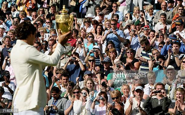 Roger Federer of Switzerland holds aloft the trophy after winning then Men's final against Rafael Nadal of Spain on day thirteen of the Wimbledon...