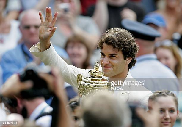 Roger Federer of Switzerland holds aloft the trophy as the crowd applaude after he won the Men's final against Rafael Nadal of Spain on day thirteen...