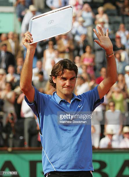 Roger Federer of Switzerland holds his runners up trophy after losing to Rafael Nadal of Spain during the Mens Singles Final on day fifteen of the...