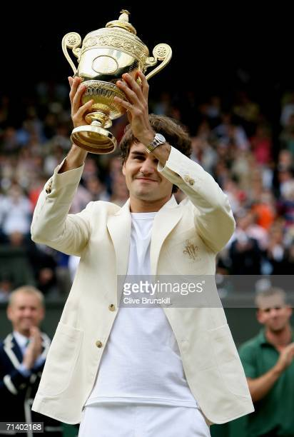 Roger Federer of Switzerland holds the aloft trophy after winning the Men's final against Rafael Nadal of Spain on day thirteen of the Wimbledon Lawn...