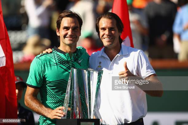 Roger Federer of Switzerland holds the BNP Paribas Open trophy with tournament director Tommy Haas after his straight sets victory against Stanislas...
