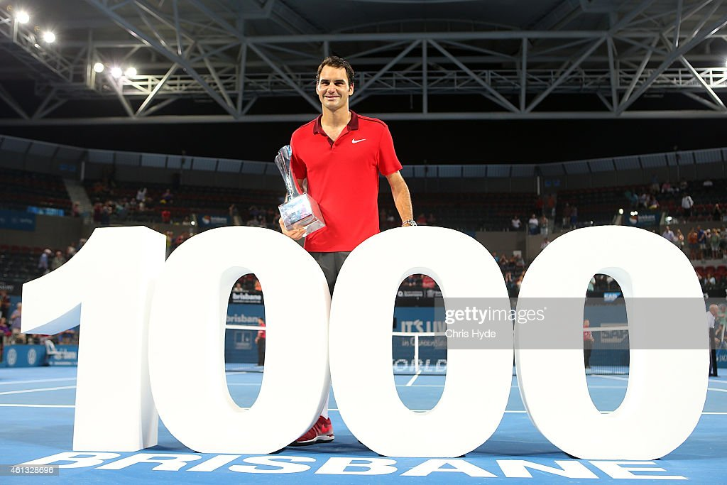 Roger Federer of Switzerland holds the Roy Emerson trophy after winning his 1000 singles title after the Mens final match against Milos Raonic of...