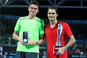 Roger Federer of Switzerland holds the Roy Emerson trophy while Milos Raonic of Canada holds the runner up trophy aftre the Mens final on day eight...