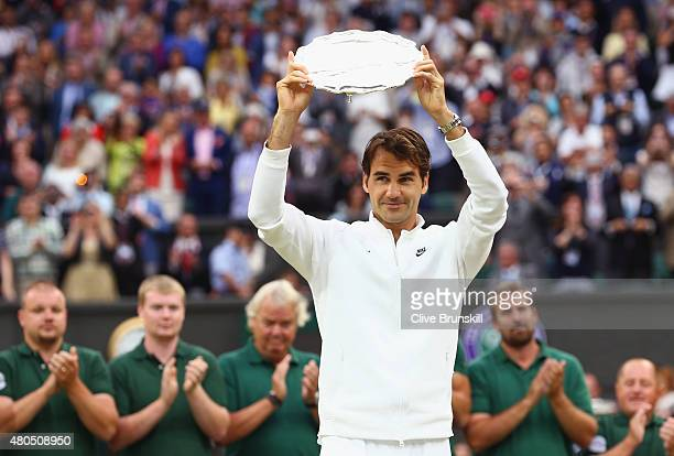 Roger Federer of Switzerland holds the runners up plate after losing in the final to Novak Djokovic of Serbia in the Final Of The Gentlemen's Singles...