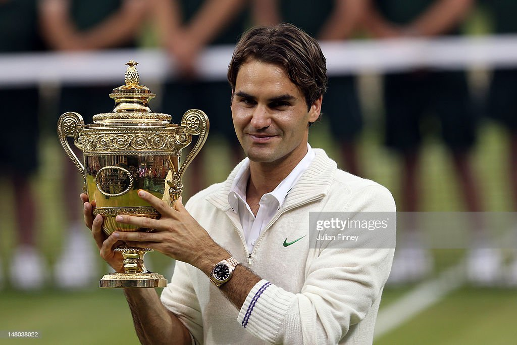 Roger Federer of Switzerland holds the winner's trophy after winning his Gentlemen's Singles final match against Andy Murray of Great Britain on day...