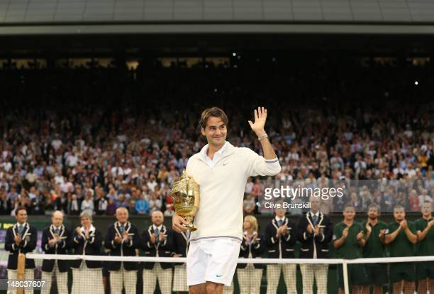 Roger Federer of Switzerland holds the winner's trophy and waves to the crowd after winning his Gentlemen's Singles final match against Andy Murray...