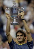 Roger Federer of Switzerland holds up the championship trophy after defeating Andre Agassi in the men's final of the US Open at the USTA National...