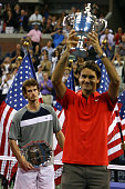 Roger Federer of Switzerland holds up the trophy as Andy Murray of the United Kingdom looks on after the 2008 US Open Men's Championship Match in...
