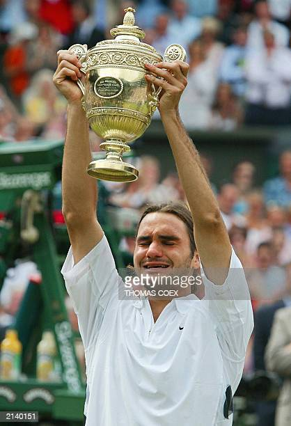 Roger Federer of Switzerland holds up the Wimbledon trophy after defeating Mark Philippoussis of Australia in their Men's Final match at the...