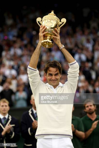 Roger Federer of Switzerland holds up the winner's trophy after winning his Gentlemen's Singles final match against Andy Murray of Great Britain on...