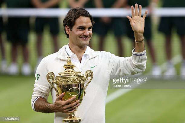 Roger Federer of Switzerland holds up the winner's trophy and waves to the crowd after winning his Gentlemen's Singles final match against Andy...
