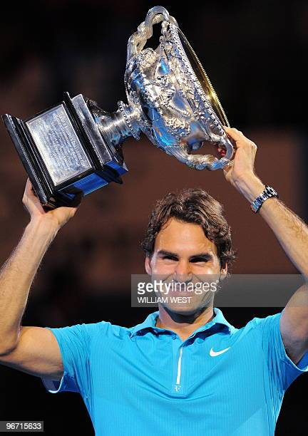 Roger Federer of Switzerland holds up the winner's trophy following his victory over Andy Murray of Britain in their men's singles final on day 14 of...