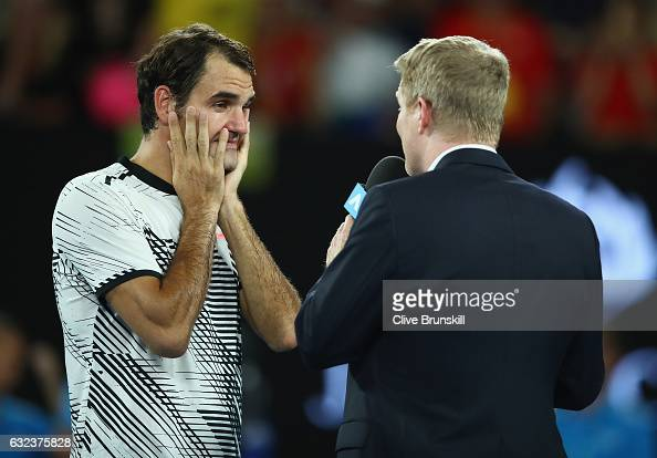 Roger Federer of Switzerland interviewed for tv by Jim Courier after victory in his fourth round match against Kei Nishikori of Japan on day seven of...