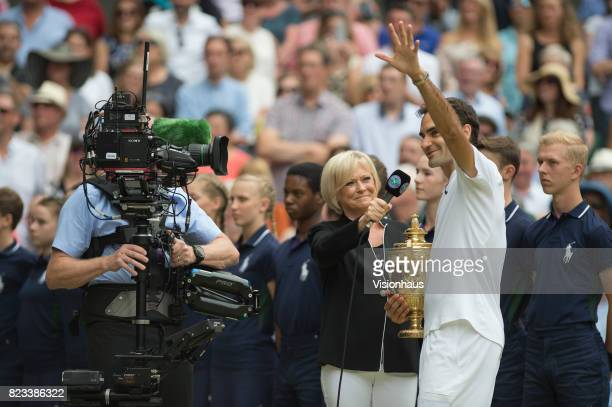 Roger Federer of Switzerland is interviewed by Sue Barker of the BBC after winning the Men's Singles Final against Marin Cilic on day thirteen of the...