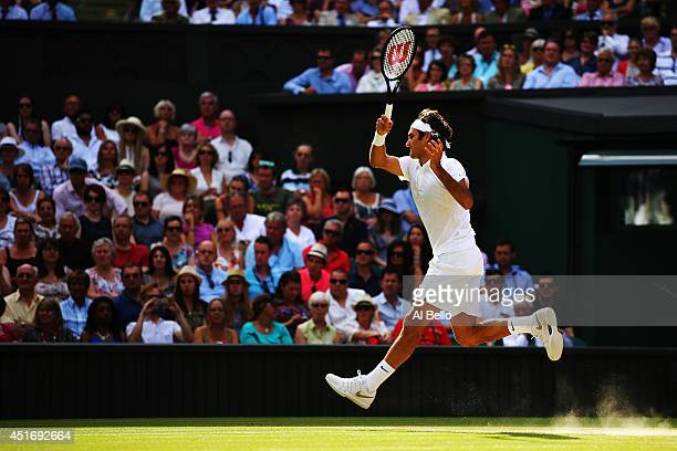 Roger Federer of Switzerland jumps to make a return during his Gentlemen's Singles semifinal match against Milos Raonic of Canada on day eleven of...