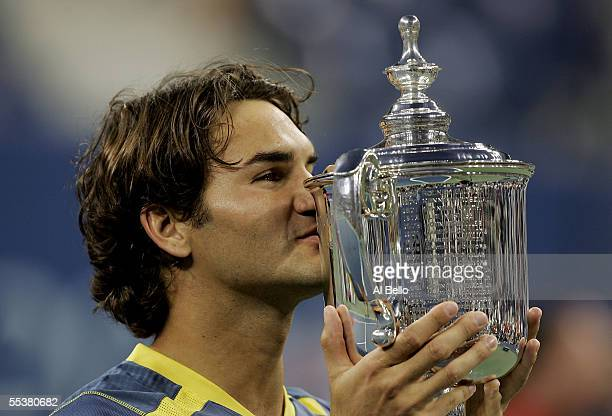Roger Federer of Switzerland kisses the championship trophy after defeating Andre Agassi in the men's final of the US Open at the USTA National...
