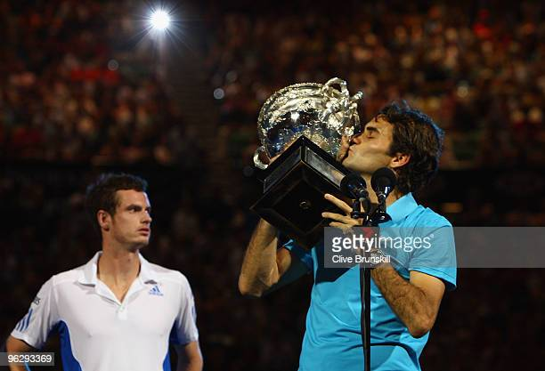 Roger Federer of Switzerland kisses the Norman Brookes Challenge Cup as Andy Murray of Great Britain looks on after the men's final match during day...