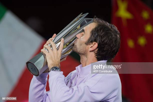 TOPSHOT Roger Federer of Switzerland kisses the trophy after winning his men's final singles match against Rafael Nadal of Spain at the Shanghai...