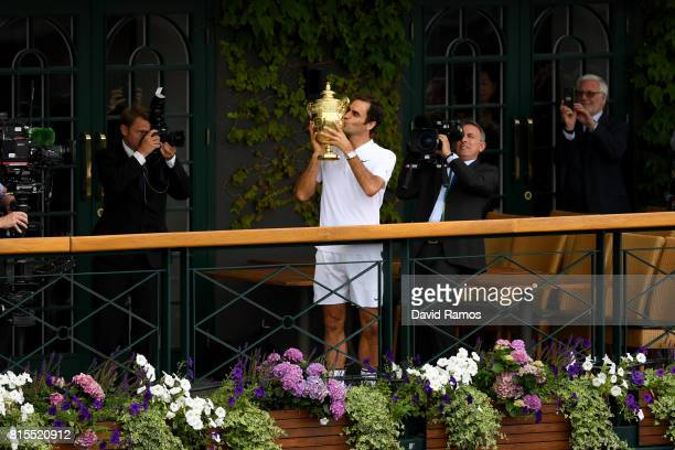 Roger Federer of Switzerland kisses the trophy as he celebrates victory on the balcony after the Gentlemen's Singles final against Marin Cilic of...