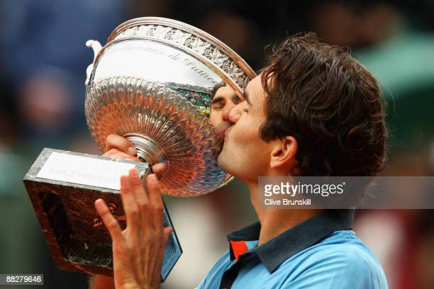 Roger Federer of Switzerland kisses the trophy as he celebrates victory during the Men's Singles Final match against Robin Soderling of Sweden on day...