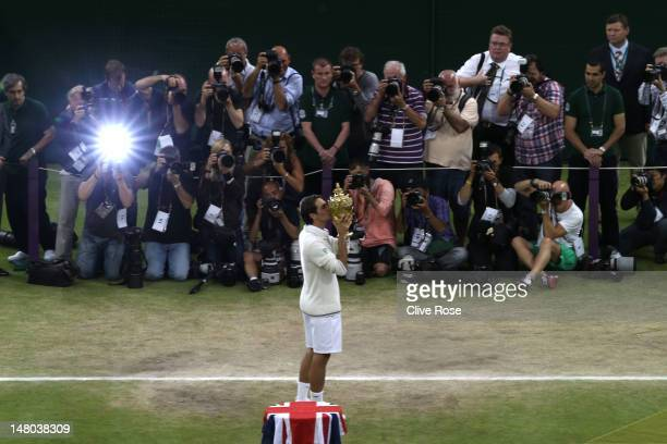 Roger Federer of Switzerland kisses the winner's trophy after winning his Gentlemen's Singles final match against Andy Murray of Great Britain on day...