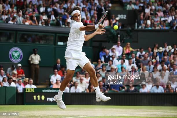 Roger Federer of Switzerland leaps to hit a forehand return during his Gentlemen's Singles quarterfinal match against Stan Wawrinka of Switzerland on...