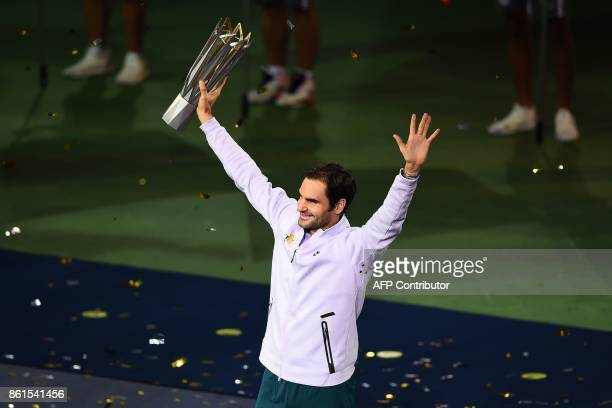 Roger Federer of Switzerland lifts his trophy after winning the men's singles final match against Rafael Nadal of Spain at the Shanghai Masters...
