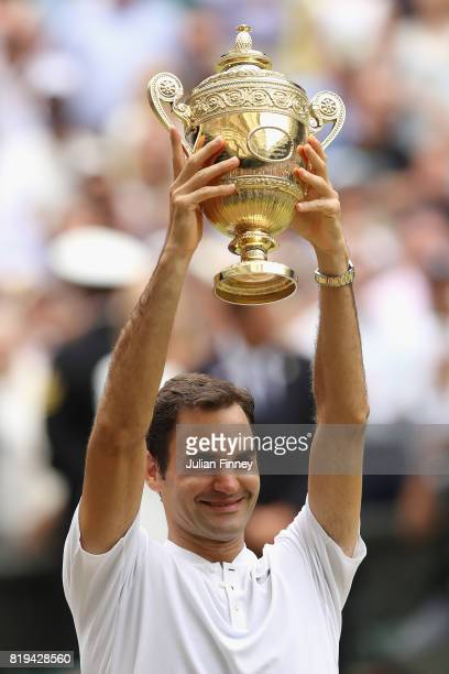 Roger Federer of Switzerland lifts the trophy as he celebrates victory after the Gentlemen's Singles final against Marin Cilic of Croatia on day...