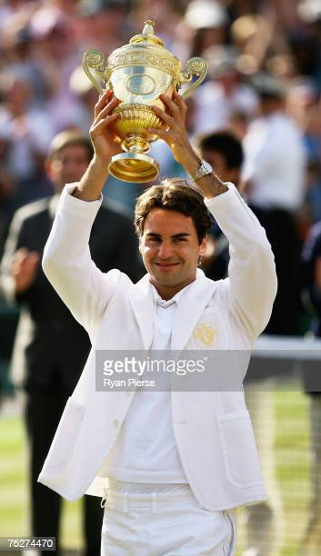 Roger Federer of Switzerland lifts the trophy as he celebrates victory following the Men's Singles final match against Rafael Nadal of Spain during...