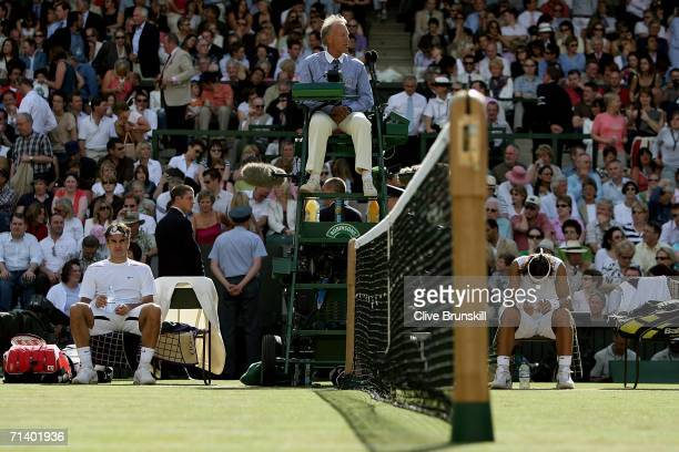 Roger Federer of Switzerland looks on during a break with Rafael Nadal of Spain during the men's final on day thirteen of the Wimbledon Lawn Tennis...