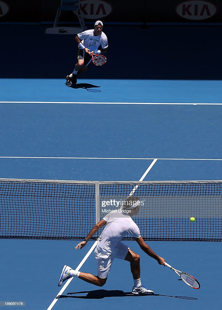 Roger Federer of Switzerland plays a forehand volley against Lleyton Hewitt of Australia during practice ahead of the 2013 Australian Open at Melbourne Park on January 8, 2013 in Melbourne, Australia.
