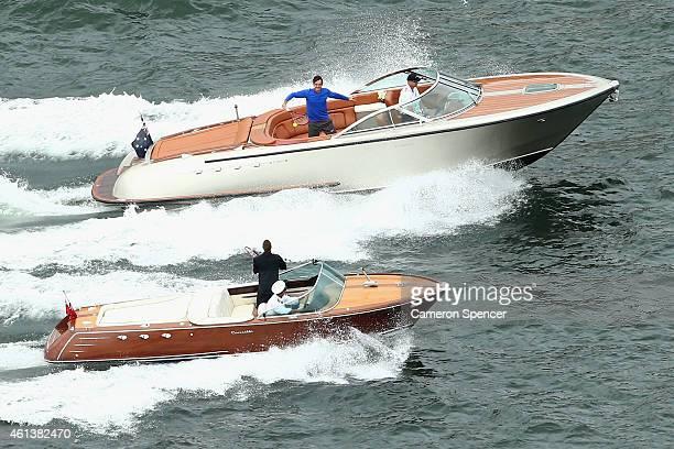 Roger Federer of Switzerland plays tennis with Lleyton Hewitt of Australia between speedboats on Sydney Harbour ahead of their Fast 4 Exhibition...