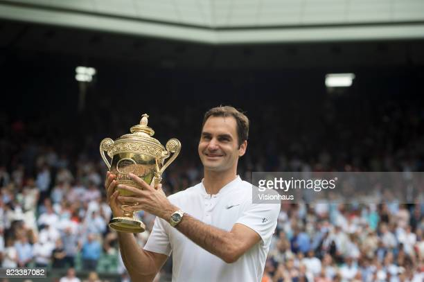 Roger Federer of Switzerland poses for photographs as he celebrates winning the Men's Singles Final against Marin Cilic on day thirteen of the...