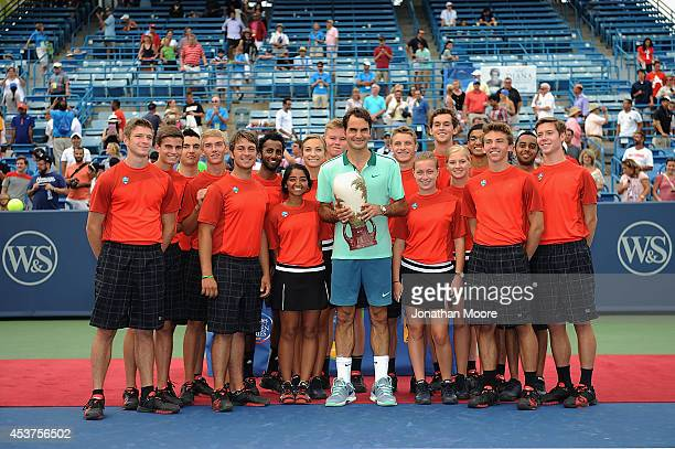 Roger Federer of Switzerland poses with ball boys after winning a final match against David Ferrer on day 9 of the Western Southern Open at the...