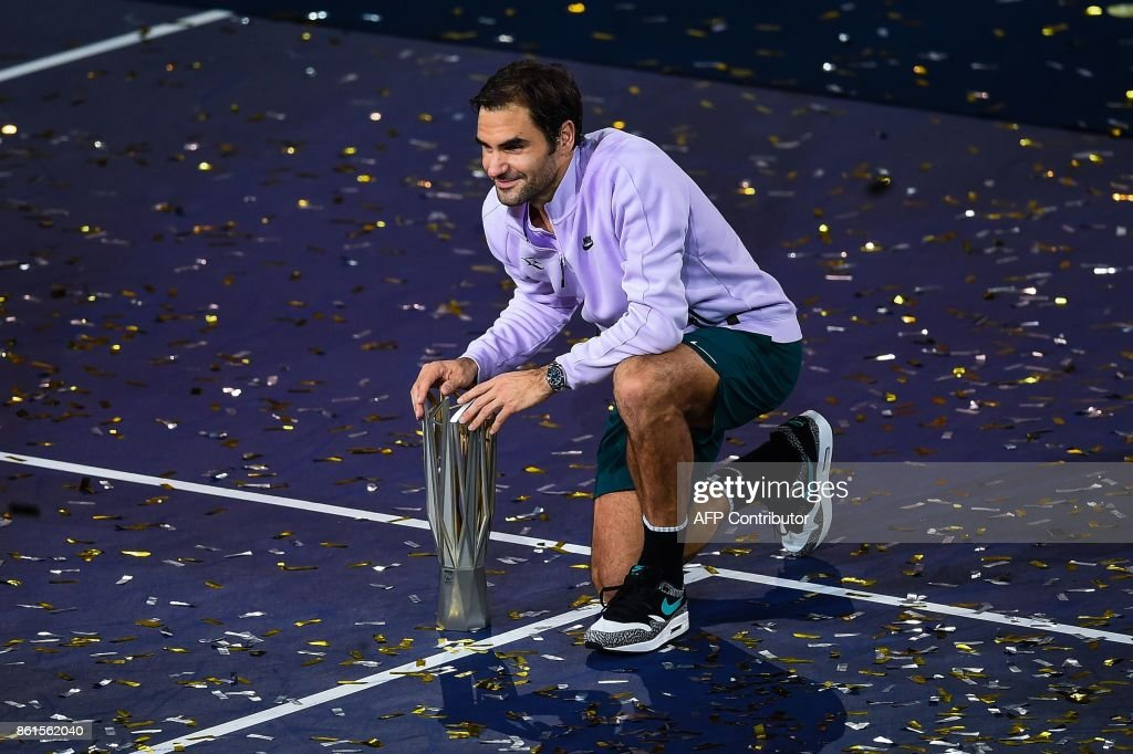TOPSHOT - Roger Federer of Switzerland poses with his trophy after beating Rafael Nadal of Spain in the men's singles final match at the Shanghai Masters tennis tournament in Shanghai on October 15, 2017. / AFP PHOTO / Chandan KHANNA