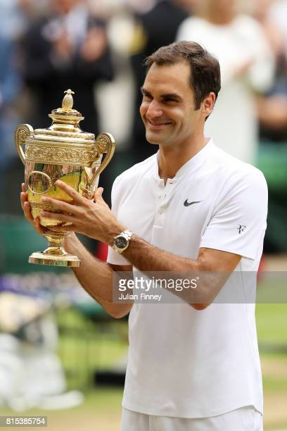 Roger Federer of Switzerland poses with the trophy as he celebrates victory after the Gentlemen's Singles final against Marin Cilic of Croatia on day...