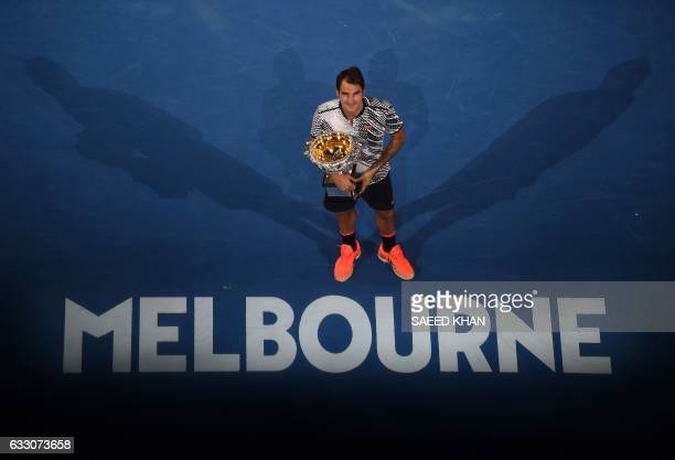 Roger Federer of Switzerland poses with the winner's trophy following his victory over Rafael Nadal of Spain in the men's singles final on day 14 of...