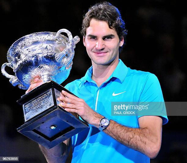 Roger Federer of Switzerland poses with the winner's trophy following his victory over Andy Murray of Britain in their men's singles final on day 14...